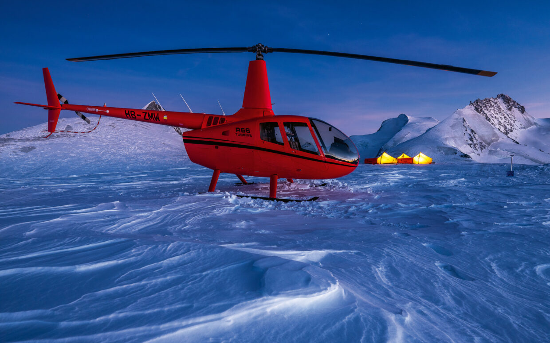 Mit dem letzten Tageslicht beleuchtet, scheint der Sundance.swiss Helikopter in kräftigem orange. Die drei Schlafzelte im Hintergrund sind gelb beleuchtet und geben dem Bild Wärme. Der Gletscher Schnee ist zerfurcht.