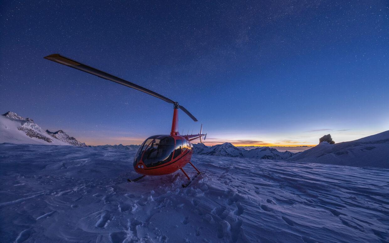 Es ist noch Nacht, aber der neue Tag zeichnet sich am östlichen Horizont mit einem dünnen hell gelben Streifen an. Die Milchstrassen Galaxie ist noch leicht sichtbar. Der Sundance.swiss Heli steht geparkt auf dem Gletscher. Es ist -25 Grad Celsius kalt.