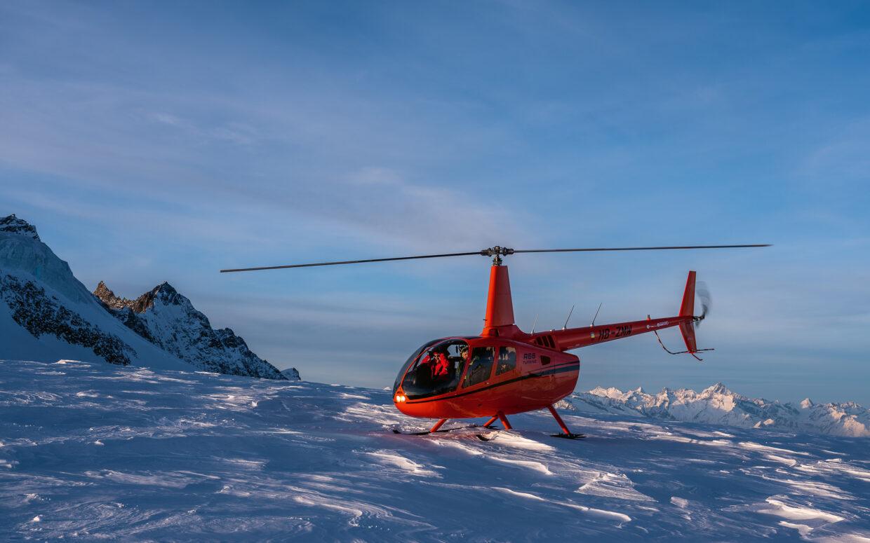 Der orange Robinson R66 Helikopter von Sundance.swiss startet um vor dem Sonnenuntergang letzte Fotos des Bergpanoramas von Saas Fee und Zermatt zu machen.