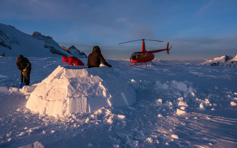 Die Sundance Crew baut ein grosses Iglu für die Übernachtung. Im Hintergrund befindet sich der Robinson R66 Helikopter in der Abendsonne.